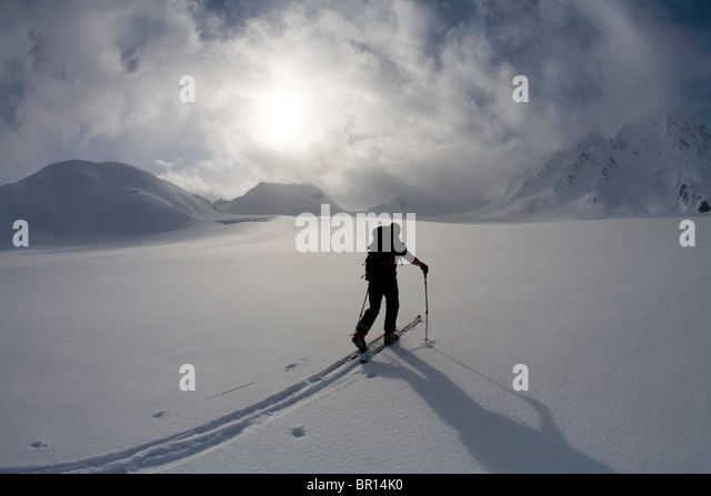 Backcountry skier crosses glacier under late day stormy sky. - Stock Image