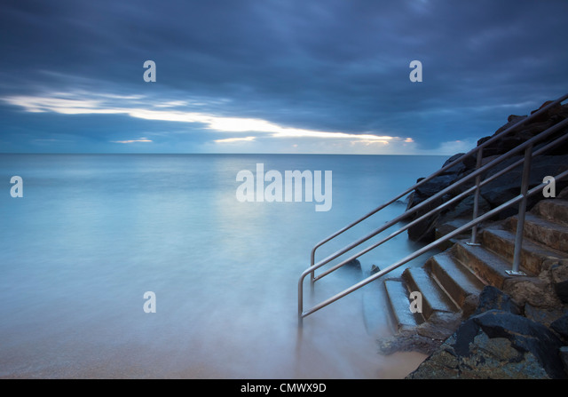 Waves washing over steps leading into sea.   Machans Beach, Cairns, Queensland, Australia - Stock Image