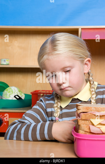Girl looking at lunch box - Stock Image