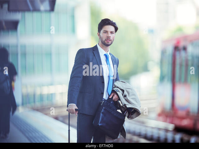 Businessman waiting at train station - Stock Image
