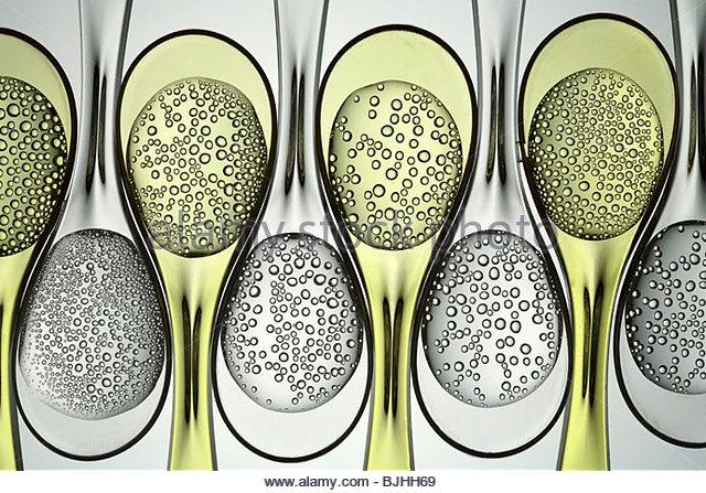 Carbonated liquids in plastic spoons - Stock Image