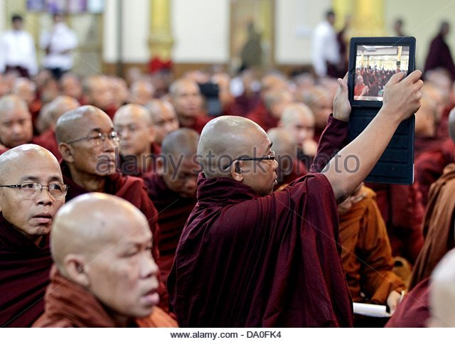 epa03762226 A Buddhist monk takes a photo with his iPad tablet computer during the Buddhist monks conference in - Stock Image