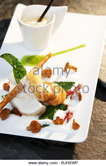 Fried monkfish with mushrooms, cappuccino in background - Stock Image