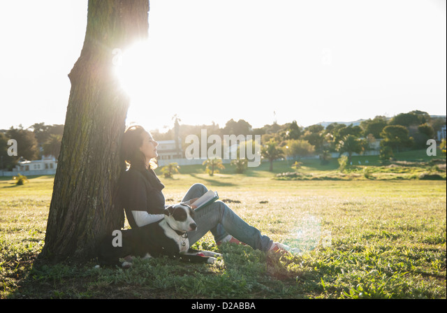 Woman relaxing with dog in park - Stock Image