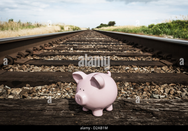 Piggy bank on railroad tracks - Stock Image