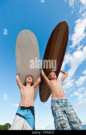 Spain, Mallorca, Children with surfboard on beach - Stock Image