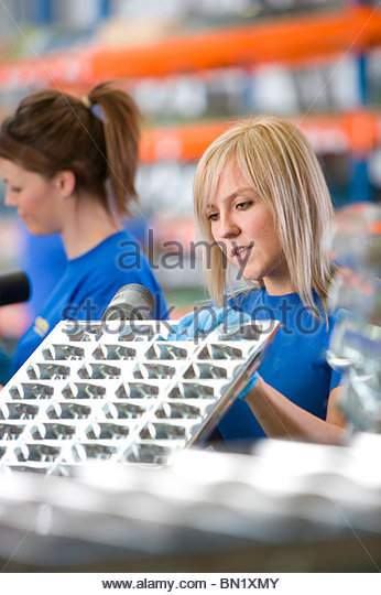 Worker drilling aluminium light fittings in factory - Stock Image