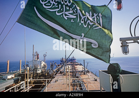 Saudi Arabian flag flies over ship loading oil. 'There is one God but God' it proclaims, with a sword beneath - Stock Image