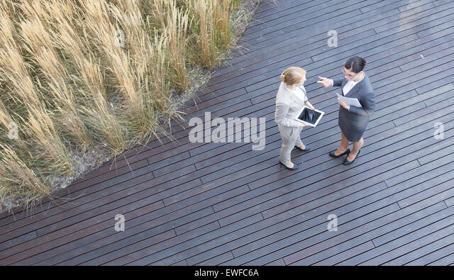 High angle view of businesswomen discussing while standing on floorboard - Stock Image