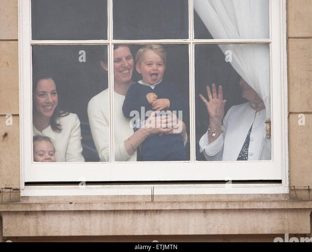 Britian's Prince George is held by a nanny as he waves through a window of Buckingham Palace 13 June 2015 while - Stock Image