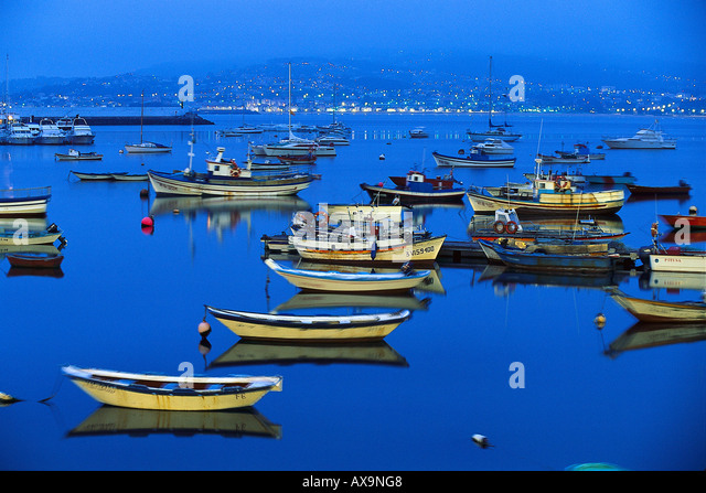Fishing boats in the harbour at night, Ria de Baiona, Pontevedra, Galicia, Spain - Stock Image