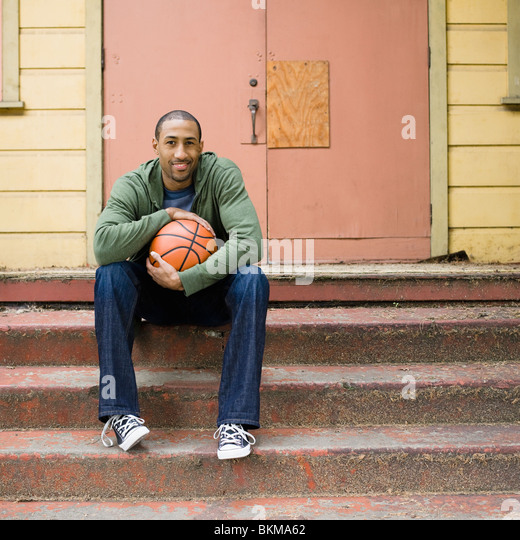 African American man sitting on steps with basketball - Stock Image