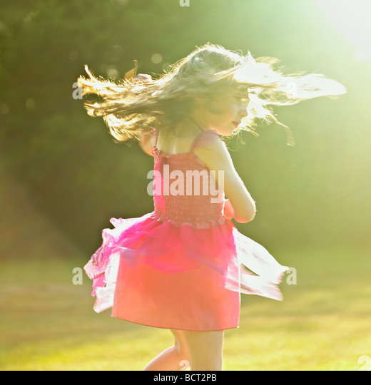 Young girl dancing in the summer sun. - Stock Image