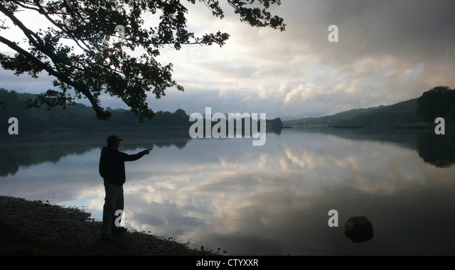 Man looking out over still lake - Stock Image