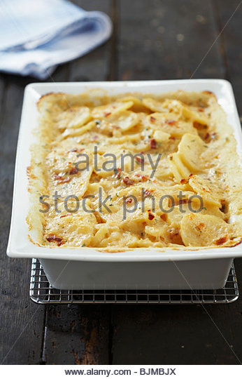 Scalloped Potatoes with Bacon and Cheese in Baking Dish - Stock Image