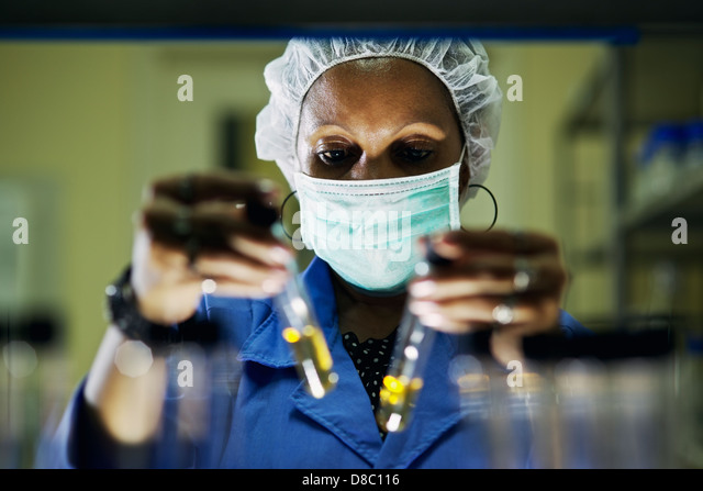 Science and research, woman working as chemist looking at test tube in laboratory - Stock Image