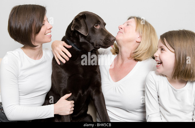 Shot of Three Generations of a Family Laughing with their Dog - Stock Image