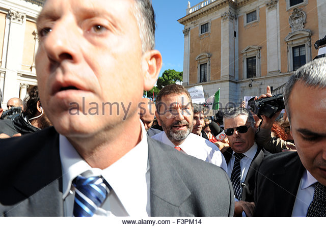 Rome Italy 11th October 2015 A large group of protesters gather in front of the Campidoglio in support of the Mayor of Rome Ignazio Marino after he resigned amidst an expense scandal. According to many in the crowd Marino is responsible for cleaning up the city from corruption.   Surrounded by security and press Marino (centre - red tie) crosses the square through his supporters. - Stock Image