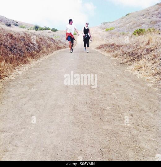 Guy and girl walking along trail - Stock Image