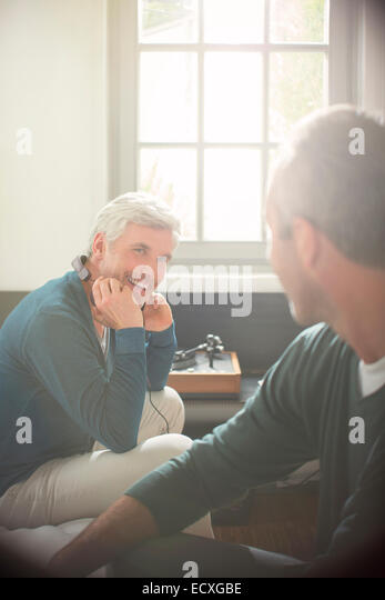 Men relaxing together in living room - Stock Image