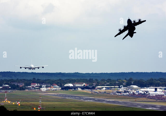 Airbus A380-841 landing and Airbus A400M Atlas taking off at runway of Farnborough International Airshow 2014 - Stock Image