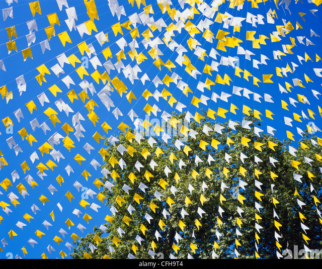 YELLOW & WHITE BUNTING AGAINST DEEP BLUE SKY AND TREE, RADIATING OUT FROM TOP RIGHT-HAND CORNER - Stock Image