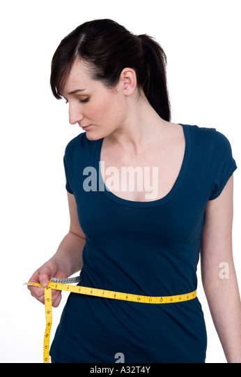 young woman measuring her waist with a tape measure - Stock Image
