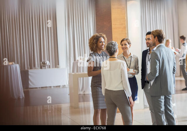 Business people standing in conference room, talking and smiling - Stock Image