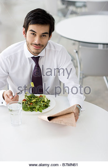 A man reading a newspaper whilst having his lunch - Stock Image