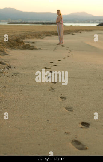 young-girl-looks-back-at-her-footprints-