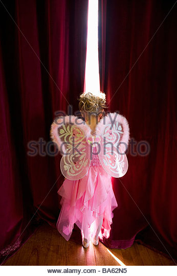 Girl (4-6) with fairy wings looking out gap in curtains, rear view - Stock Image