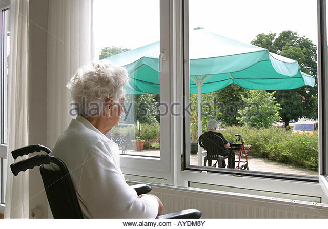 Old woman on a wheelchair looking through a window - Stock Image