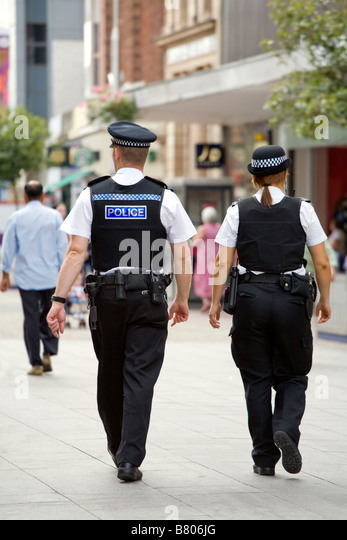 BACK VIEW OF TWO POLICE OFFICERS, MALE AND FEMALE, WALKING DOWN THE HIGH STREET IN SOUTHEND ON SEA. - Stock Image