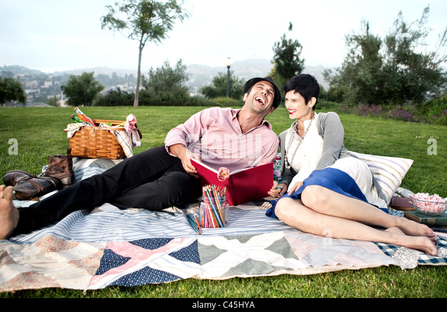 Barefoot, stylish couple relaxing and picnicking on a lush green lawn of a park. The man is laughing and sketching - Stock Image