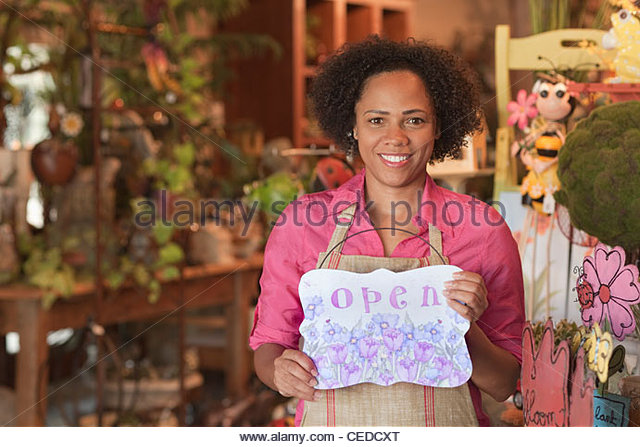 African American business owner standing in shop holding open sign - Stock Image