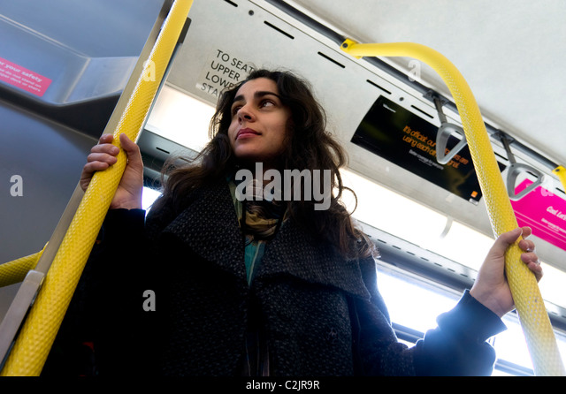 Low angle view of young woman riding a London bus - Stock Image
