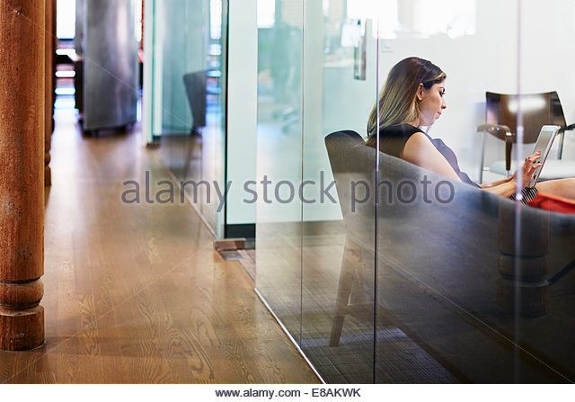 Young woman on sofa using tablet in office - Stock Image