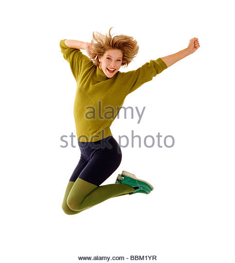 Young woman jumping athletically, wearing green sweater and tight shorts. - Stock Image