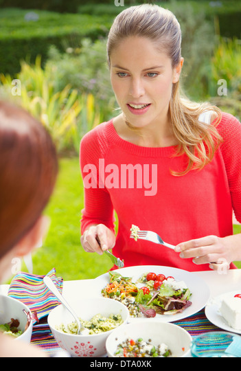 Woman Having Lunch in Garden with Friend - Stock Image