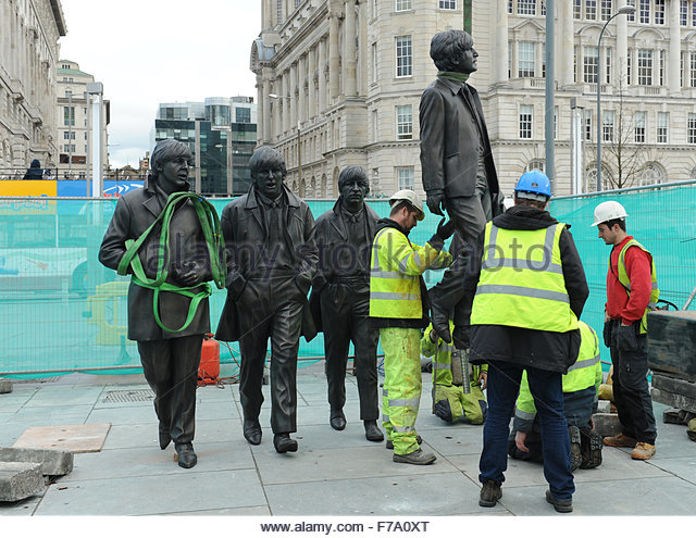 Liverpool, UK. 27th November, 2015. Opposite the Mersey Ferry terminal on the quayside workmen place a sculpture of perhaps the most famous sons of the city, the Beatles. As work commences John Lennon hangs somewhat unceremoniously from the crane. - Stock Image