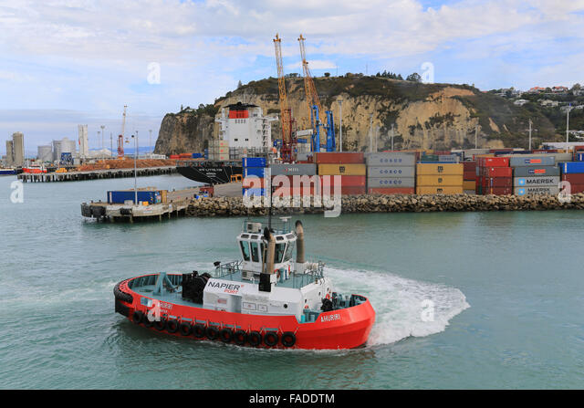Napier Port tug Ahuriri maneuvers in the harbour while the freighter NYK Lyttelton unloads a cargo of containers. - Stock Image