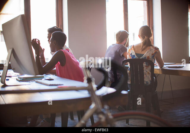 Creative business people working in open office plan - Stock Image