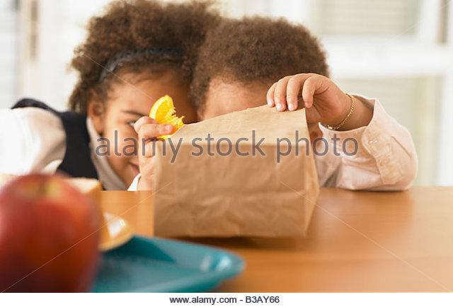 African siblings looking in bag lunch - Stock Image