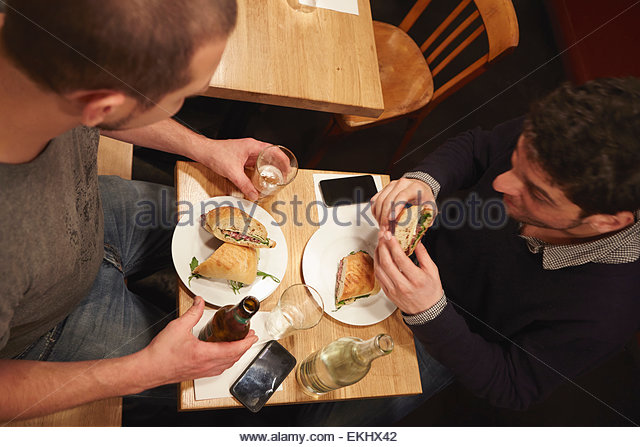 Two men having lunch in restaurant, elevated view - Stock Image