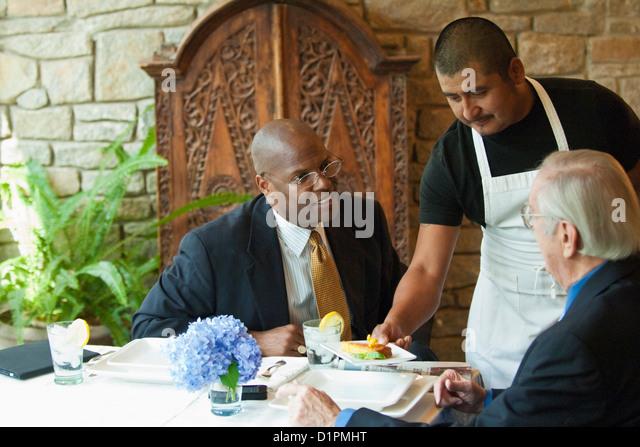 Businessmen having lunch in restaurant - Stock Image