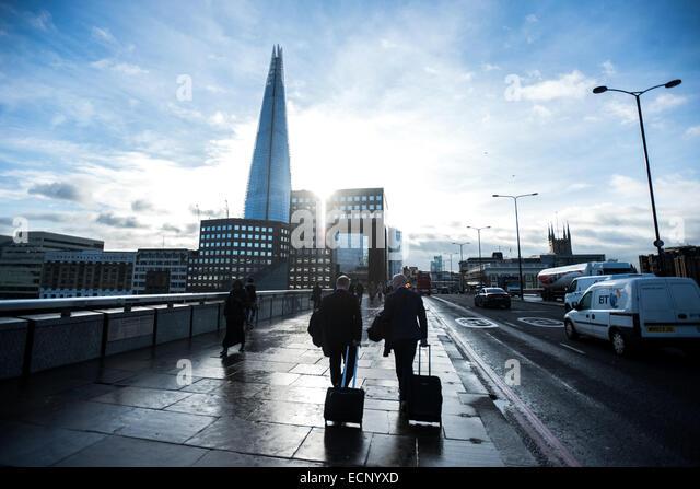 London, UK - 17 December 2014: businessmen with trolleys cross London Bridge as the sun shines behind buildings - Stock Image