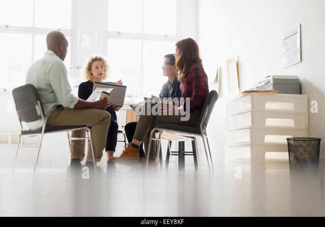Friends having business meeting in office - Stock Image