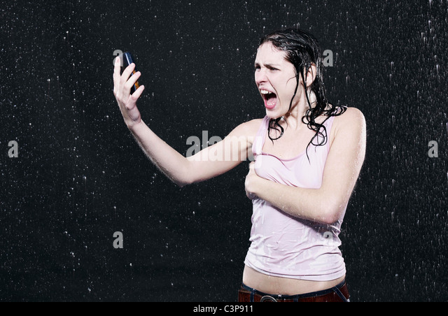 Woman looking at mobile phone, mouth open. - Stock Image