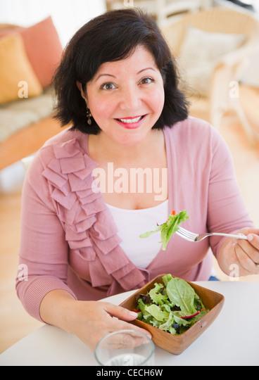 Hispanic woman eating salad for lunch - Stock Image