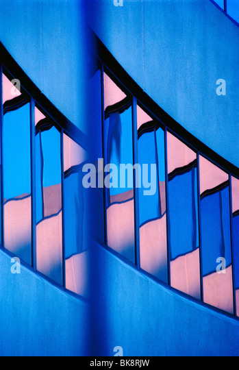 Abstract view of a modern corporate office building including reflections in the windows of the sunset sky - Stock Image